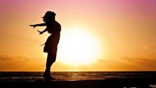 夕日と手を広げる女性